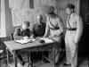 Φωτογραφία του 1945 όπου δείχνει τον Γερμανό διοικητή της περιφέρειας του Αιγαίου, στρατηγό Βάγκνερ, να υπογράφει στο κοινοτικό γραφείο της Σύμης, την παράδοση των Δωδεκανήσων παρουσία των Βρετανών.