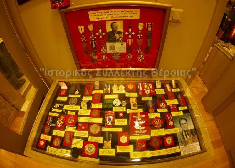Μία εκ των πολλών επιτραπέζιων βιτρινών του ''Βλαχογιάννειου'' μουσείου με Ελληνικά εμβλήματα και διακριτικά, καθώς και κορνίζα με μετάλλια και διακρίσεις ανώτατου αξκου.