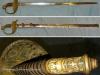 Το σπάνιο ελληνικό ξίφος του ''Πεζικού Mod.1868'' των ελλήνων αξιωματικών, το οποίο στο πίσω μέρος της χειρολαβής, καθώς και στο προστατευτικό πάνω μέρος της χειρολαβής φέρει ανάγλυφο τον ''βασιλικό θυρεό'', ενώ η λάμα φέρει σε σκαλιστό το ρητό ''ΑΜΥΝΕΣΘΑΙ ΠΕΡΙ ΠΑΤΡΗΣ'' ,και εκ νέου τον ''βασιλικό θυρεό'' καθώς και διάφορα σκαλίσματα.